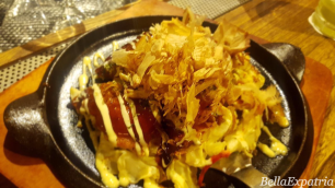 Seafood okonomiyaki up close, with generous heaps of bonito flakes